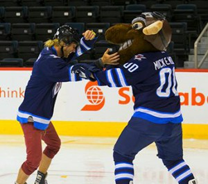 Mickey dances with Mick E Moose after beating Natalie Spooner and Meaghan Mikkelson at a hockey challenge on Amazing Race Canada 2 episode 6